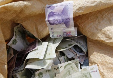 Chinese Yuan bank notes are seen in a vendor's cash sack at a market in Beijing April 10, 2013. REUTERS/Kim Kyung-Hoon