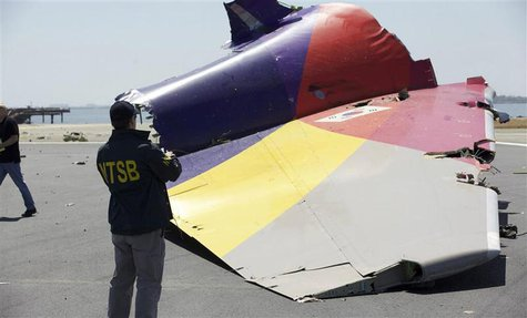 A National Transportation Safety Board (NTSB) investigator looks at the tail section of the Asiana Airlines Flight 214 that crashed at San F