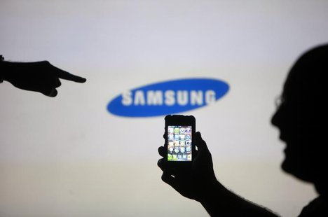 Men are silhouetted against a video screen with an Samsung logo as they pose with an Apple iPhone 4 smartphone in this photo illustration ta