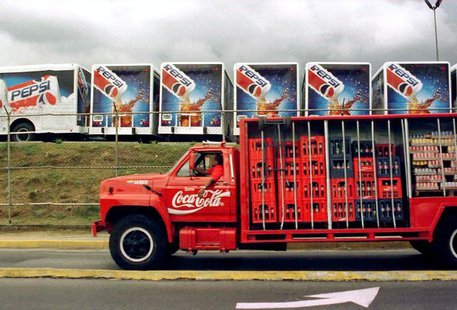 A Coca Cola truck passes in front of a Pepsi Co. parking lot filled with new Pepsi Cola trucks December 9.
