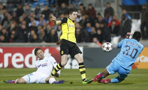 Marseille goalkeeper Steve Mandanda (R) fails to catch the ball as Borussia Dortmund's Robert Lewandowski scores the first goal against Olym