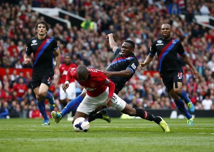 Manchester United's Ashley Young (L) is fouled by Crystal Palace's Kagisho Dikgacoi during their English Premier League soccer match at Old