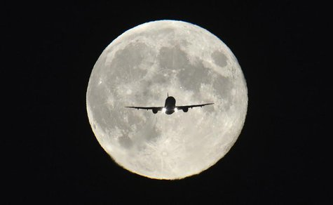 "A passenger aircraft, with the full ""Harvest Moon"" seen behind, makes its final approach to landing at Heathrow Airport in west London, Sept"