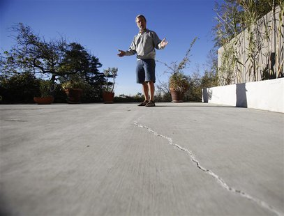 Homeowner Gary Gless looks at cracks in cement in his backyard in Los Angeles, California December 11, 2013. REUTERS/Mario Anzuoni