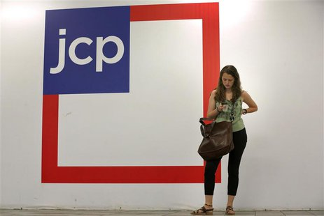 A woman checks her phone outside the entrance of a J.C. Penney store in New York in this file photo from August 14, 2013. REUTERS/Brendan Mc