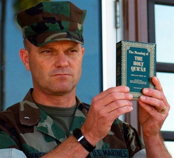 File photo of Michael Lehnert holding a copy of the Koran as he announced that they had arrived and were distributed to detainees at Camp X-
