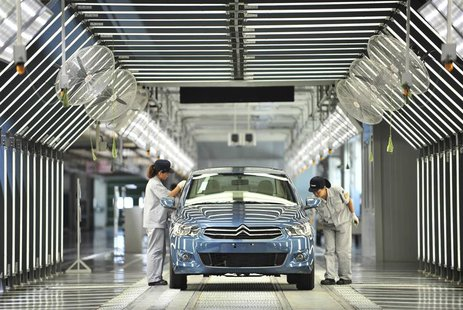 Employees work at the third factory of Dongfeng Peugeot Citroen Automobile company, after its inauguration ceremony, in Wuhan, in this July