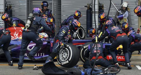 Red Bull Formula One driver Sebastian Vettel of Germany is attended to by his crew during a pit stop during the Brazilian F1 Grand Prix at t