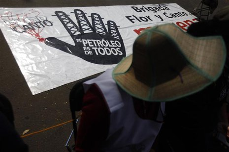 A demonstrator sits next to a banner at the perimeter of the Congress building during a demonstration against the energy reform bill in Mexi