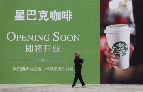 A man walks past an advertisement board of Starbucks in Wuhan, Hubei province, in this October 29, 2013 file photo. REUTERS/Stringer