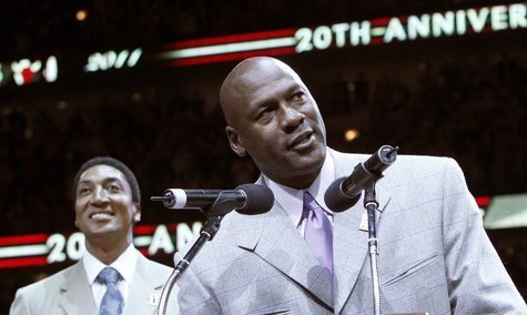Former Bulls star Michael Jordan (R) talks to the crowd while Scottie Pippen looks on during a ceremony to honor the 20th anniversary of the