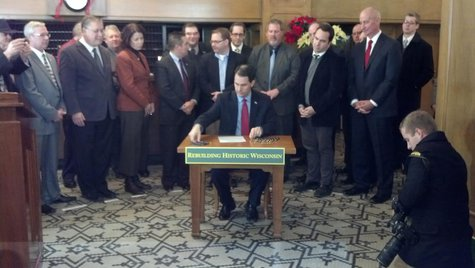 Governor Scott Walker signs the bill increasing Wisconsin's historic building restoration tax credit into law at the Hotel Northland in Green Bay on Dec. 11, 2013. (Photo by: WTAQ Reporter Jeff Flynt).