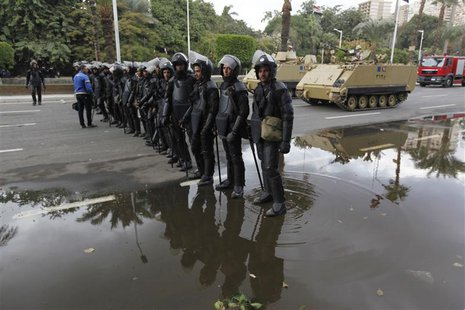 Egyptian security forces and army vehicles hold their positions outside Cairo university during clashes between riot policemen and Cairo Uni