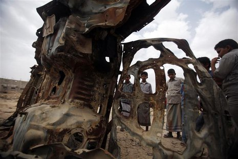 Boys gather near the wreckage of a car destroyed in 2012 by a U.S. drone air strike targeting suspected al Qaeda militants in Azan, in the s