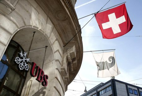 A Swiss national flag (top) and a flag of the city of Basel fly over the entrance of a branch office of Swiss bank UBS in Basel October 22,