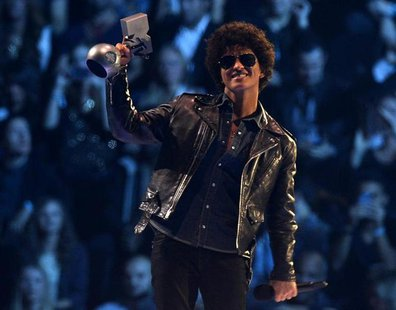 Singer Bruno Mars reacts after receiving his trophy during the 2013 MTV Europe Music Awards at the Ziggo Dome in Amsterdam November 10, 2013