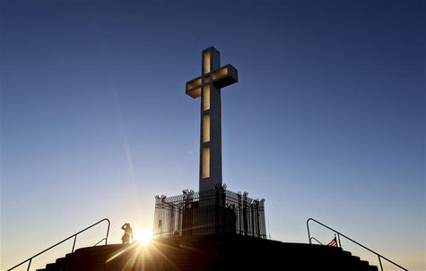 People gather in the late evening sun around the massive cross sitting atop the Mt. Soledad War Memorial in La Jolla, California on December