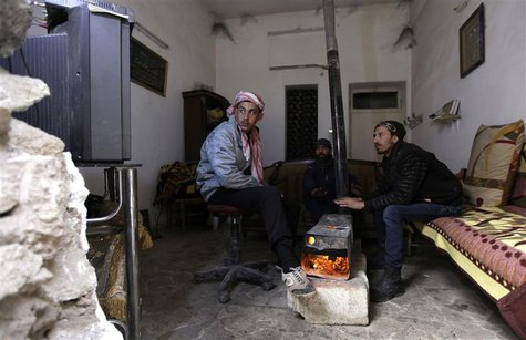 Free Syrian Army fighters warm themselves around a heater inside a room in Deir al-Zor, eastern Syria, December 12, 2013. REUTERS/Khalil Ash
