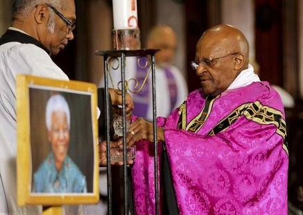 Former Archbishop of Cape Town and veteran anti-apartheid campaigner Desmond Tutu (R) holds a mass at Cape Town's Anglican St George's Cathe