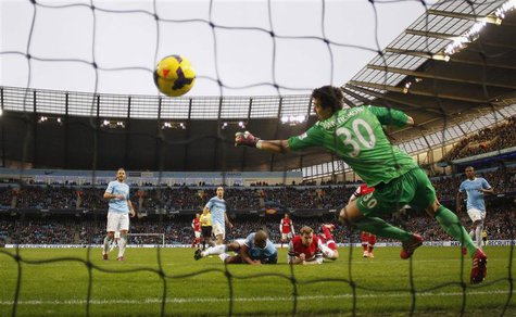 Arsenal's Per Mertesacker (C, bottom) heads and scores a goal during their English Premier League soccer match against Manchester City at th