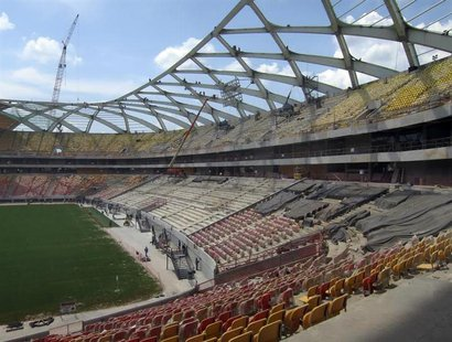 Steelworkers work on the roof structure above the pitch inside the Arena Amazonia stadium as constrcution continues in preparation for the 2