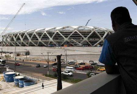 A worker observes the Arena Amazonia stadium under construction to host several 2014 World Cup soccer games, in Manaus December 14, 2013. RE