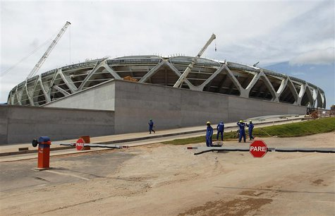Workers stand outside the Arena Amazonia stadium under construction to host several 2014 World Cup soccer games, in Manaus December 14, 2013