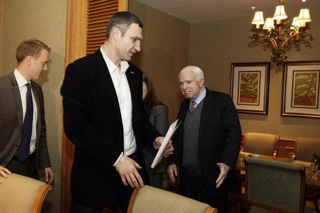 U.S. Senator John McCain (R) reacts as Ukrainian opposition leader Vitaly Klitschko (C) looks on, during their meeting in Kiev December 14,