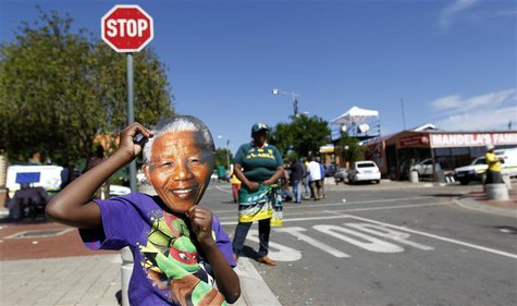 A boy wears a mask of former South African President Nelson Mandela outside his house along Vilakazi Street in Soweto, where Mandela resided