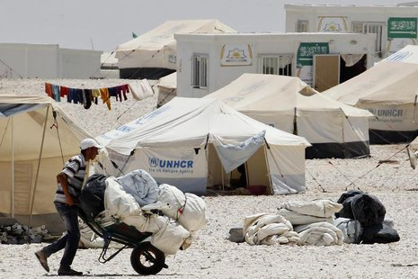 A newly arrived Syrian refugee receives aid and rations, at Al-Zaatri refugee camp in the Jordanian city of Mafraq, near the border with Syr