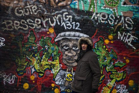 "Dimitar ""Mitko"" Todorov, a Roma from the Bulgarian city of Plevna, walks past a graffiti at a former ice factory that serves as his home in"