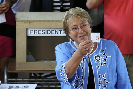 Chilean presidential candidate Michelle Bachelet shows her ballot paper during the presidential election in Santiago December 15, 2013. REUT