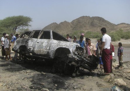 People gather at the site of a drone strike on the road between Yafe and Radfan districts of the southern Yemeni province of Lahj August 11,