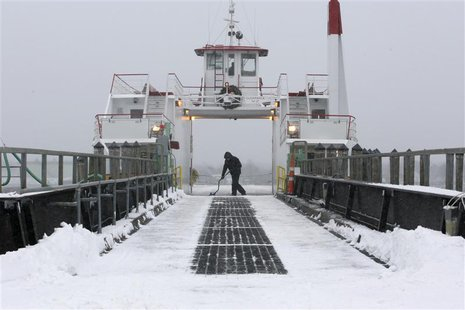 Casco Bay Lines deckhand Nick Ferrara shovels off the deck of the car ferry Machigonne II following a snowstorm in Portland, Maine December