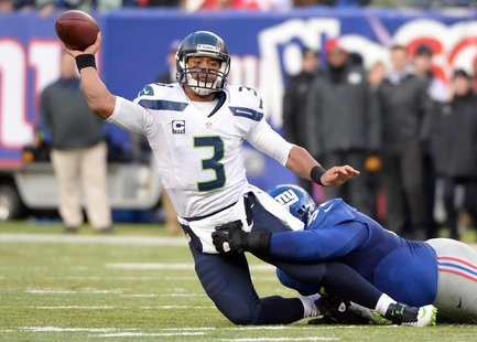 Dec 15, 2013; East Rutherford, NJ, USA; Seattle Seahawks quarterback Russell Wilson (3) throws a pass as he is taken down by New York Giants