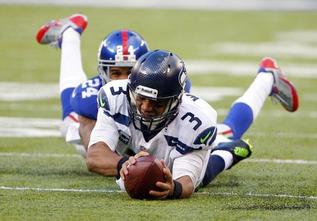 Dec 15, 2013; East Rutherford, NJ, USA; Seattle Seahawks quarterback Russell Wilson (3) dives forward for a first down as New York Giants co
