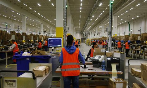 Workers handle items for delivery at Amazon's new distribution center in Brieselang, near Berlin November 28, 2013. REUTERS/Tobias Schwarz