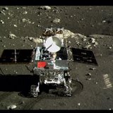 A view of China's first moon rover, Yutu, or Jade Rabbit, is seen on the lunar surface with the Chinese national flag in this still image ta