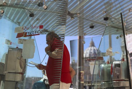 A man uses a Telecom Italia phone booth in front of St Peter's Basilica in Rome September 24, 2013. REUTERS/Alessandro Bianchi