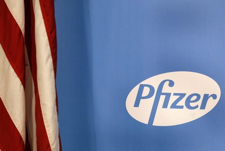 The Pfizer logo is seen next to a U.S. flag in a conference room at their world headquarters in New York November 5, 2013. REUTERS/Adam Hung
