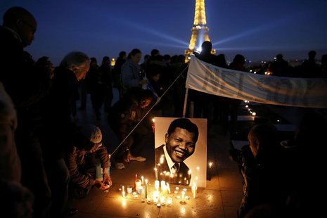 People place candles near a photo as they pay tribute to former South African President Nelson Mandela at the Trocadero square, in front of