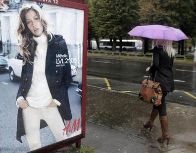 A woman walks past a H&M advertisement in Riga September 25, 2013. REUTERS/Ints Kalnins