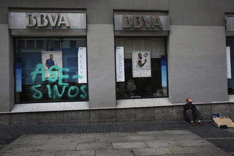 A man asks for alms outside a branch of Spanish BBVA bank in Madrid September 30, 2013. REUTERS/Susana Vera