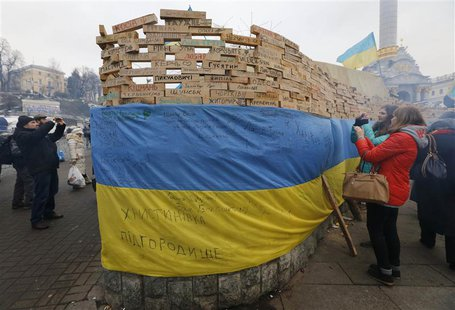 People take pictures of wooden bars, bearing names of Ukrainian cities and settlements which are hometowns of demonstrators, as Pro-European
