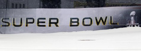 A snow bank obscures the logo for Super Bowl XLV outside Cowboy Stadium in Arlington, Texas February 4, 2011. REUTERS/Brian Snyder