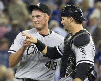 Chicago White Sox catcher A.J. Pierzynski (R) congratulates pitcher Addison Reed on the save after they beat the Toronto Blue Jays in their