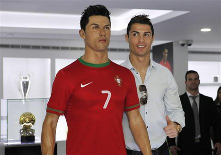 Cristiano Ronaldo, who plays for Real Madrid and Portugal's national soccer team, poses with his statue during the inauguration of his museu