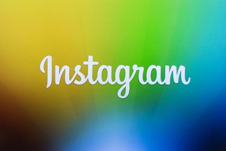 A screen displays the Instagram logo during a presentation by co-founder Kevin Systrom as he announces the launch of a new direct image mess