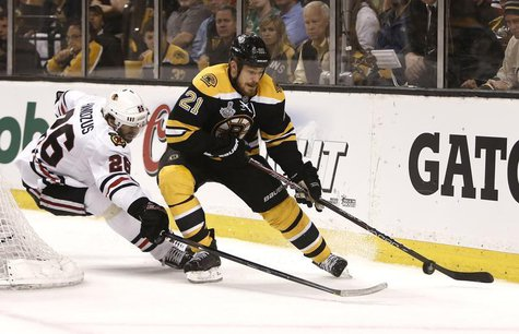 Boston Bruins right wing Shawn Thornton (22) is chased by Chicago Blackhawks center Michal Handzus (26) during the first period in Game 3 of