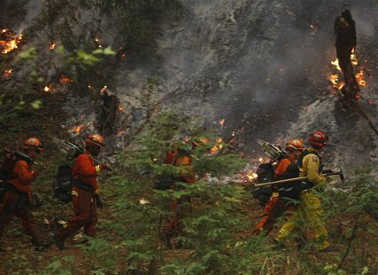 A firefighting crew walks past burning trees in Big Sur, California, December 16, 2013. REUTERS/Michael Fiala